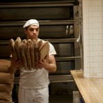 Baker carries bread from oven.